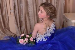 junge Prinzessin in einem blauen Kleid sitzt mit einem Blumenstrauß von ROS Lizenzfreie Stockbilder