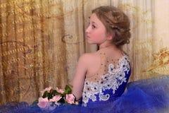 junge Prinzessin in einem blauen Kleid sitzt mit einem Blumenstrauß von ROS Lizenzfreie Stockfotos