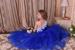 junge Prinzessin in einem blauen Kleid sitzt mit einem Blumenstrauß von ROS Stockfotos