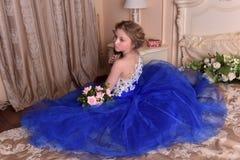 junge Prinzessin in einem blauen Kleid sitzt mit einem Blumenstrauß von ROS Lizenzfreies Stockfoto