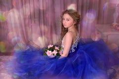 junge Prinzessin in einem blauen Kleid sitzt mit einem Blumenstrauß von ROS Stockbild