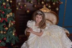 Junge Prinzessin in einem weißen Kleid mit einer Tiara auf ihrem Kopf am Weihnachtsbaum Stockfotografie