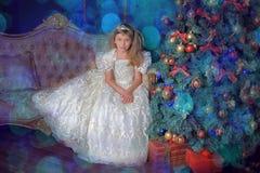 Junge Prinzessin in einem weißen Kleid mit einer Tiara auf ihrem Kopf am Weihnachtsbaum Stockfoto