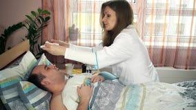 Junge professionelle weibliche Krankenschwester, die ihren geduldigen Mann liegt im Bett neigt stock footage