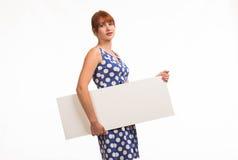 Junge rätselhafte Frau, welche die Darstellung, zeigend auf Plakat zeigt Stockfotos