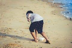Junge räumt Abfall auf dem Strand für sauberes oben umweltsmäßigkonzept auf lizenzfreies stockfoto