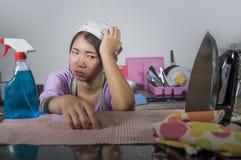 Junge recht überarbeitet und frustrierte asiatische chinesische Service-Mädchenfrau, die inländisches Reinigungs- und Reinigungsh stockfoto