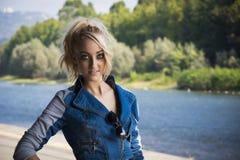 Junge-recht blonde Frau auf die modische Denim-Mode im Freien Stockfotografie
