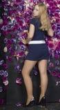 Blonde Frau der Junge recht nahe der Wand mit violetten Blumen Lizenzfreie Stockbilder
