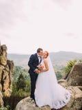 Junge redhair Braut und glücklicher Bräutigam, die weich auf dem Hintergrund von felsigen Karpatenbergen küsst Lizenzfreies Stockbild