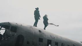 Junge reisende Paare, die auf die Oberseite des zerschmetterten Flugzeugs DC-3 in Island am windigen bewölkten Tag gehen stock video footage