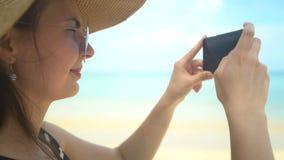 Junge Reisendfrau im Hut, der Foto auf Smartphone im Ozeanstrand macht stock video footage