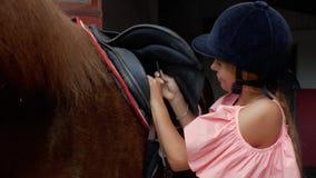 Junge Reiterin in Reitensturzhelm befestigt die Bügel auf dem Sattel, Nahaufnahme 4K Video 4K stock footage