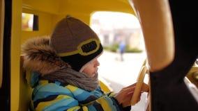 Junge reitet ein Spielzeugauto auf das Karussell stock video footage