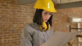 Junge reizend Architektenfrau, die Papier hält und vorwärts, konzentriert, Backsteinbauhintergrund schaut stock video