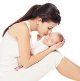 Junge reizende Mutter, die Baby küsst Stockbilder