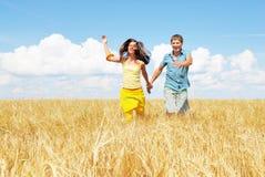 Junge reizende Paare auf einem Blumenfeld stockbilder
