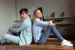 Junge reizende Paare, die auf dem Tisch zurück zu Rückseite sitzen stockbilder