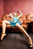 Junge reizvolle Frau auf einem Luxuxsofa Lizenzfreie Stockfotografie