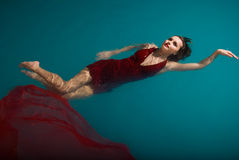 Junge reizvolle Frau, die auf Swimmingpool im Rot schwimmt Lizenzfreie Stockbilder