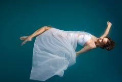Junge reizvolle Frau, die auf Swimmingpool schwimmt lizenzfreie stockfotografie