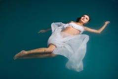 Junge reizvolle Frau, die auf Swimmingpool schwimmt stockfotografie