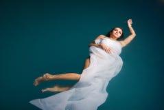 Junge reizvolle Frau, die auf Swimmingpool schwimmt Stockfotos