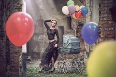 Junge reizvolle Frau mit Ballonen und Kinderwagen lizenzfreies stockfoto