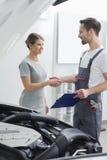 Junge Reparaturarbeitskraft, die Hände mit Kunden in der Autowerkstatt rüttelt Stockfotografie