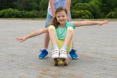 Junge rollt ein Mädchen auf einem Skateboard im Stadtpark Lizenzfreies Stockfoto