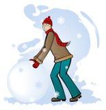 Junge rollt einen Schneeklumpen Stockbilder