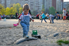 Junge rollt Spielzeugauto auf dem Spielplatz Stockfoto