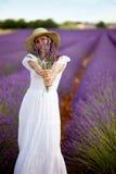 Junge romantische Frau, die auf dem Lavendelgebiet zeigt ein bouqut steht Stockfoto