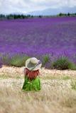 Junge romantische Frau, die vor violettem Lavendelfeld I sitzt Lizenzfreies Stockbild