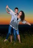 Junge romantische Paare öffnen Arme und Habenspaß bei Sonnenuntergang auf, schöner Landschaft im Freien und bewölktem Himmel, Lie Lizenzfreie Stockfotos