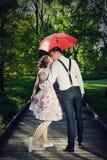 Junge romantische Paare in der Liebe, die im Regen flirtet Roter Regenschirm Lizenzfreie Stockbilder