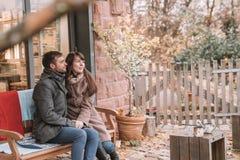 Junge romantische Paare, die auf der Bank sitzen Lizenzfreie Stockbilder