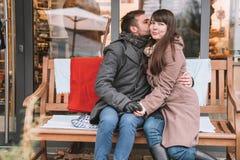 Junge romantische Paare, die auf der Bank und der bewundern erstaunlichen Natur sitzen Lizenzfreie Stockbilder