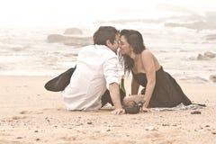 Junge romantische Paare, die auf Strand küssen Stockfotos
