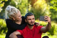 Junge romantische Paare, die draußen selfie machen Stockbilder