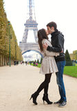 Junge romantische Paare, die nahe Eiffelturm küssen Lizenzfreie Stockbilder
