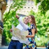Junge romantische Paare unter Verwendung der Karte nahe dem Eiffelturm in Paris, Frankreich Lizenzfreie Stockfotos