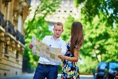 Junge romantische Paare unter Verwendung der Karte in Paris, Frankreich Lizenzfreie Stockbilder