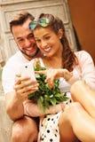 Junge romantische Paare unter Verwendung des Smartphone in der Stadt Lizenzfreie Stockfotografie