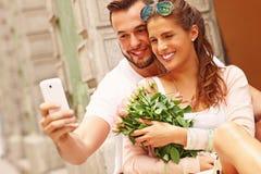 Junge romantische Paare unter Verwendung des Smartphone in der Stadt Lizenzfreie Stockbilder