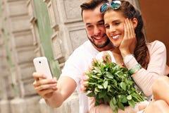 Junge romantische Paare unter Verwendung des Smartphone in der Stadt Stockbild