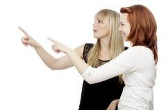 Junge rote und blonde behaarte Mädchen, die nach rechts zeigen Lizenzfreie Stockfotografie