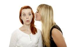 Junge rote und blonde behaarte Mädchen erklärt ein Geheimnis Stockbilder