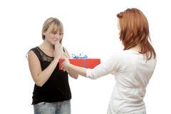 Junge rote und blonde behaarte Mädchen geben Geschenk Lizenzfreie Stockfotos