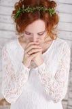 Junge rothaarige Braut in einem grünen Kranz leicht lächelnd Stockfoto